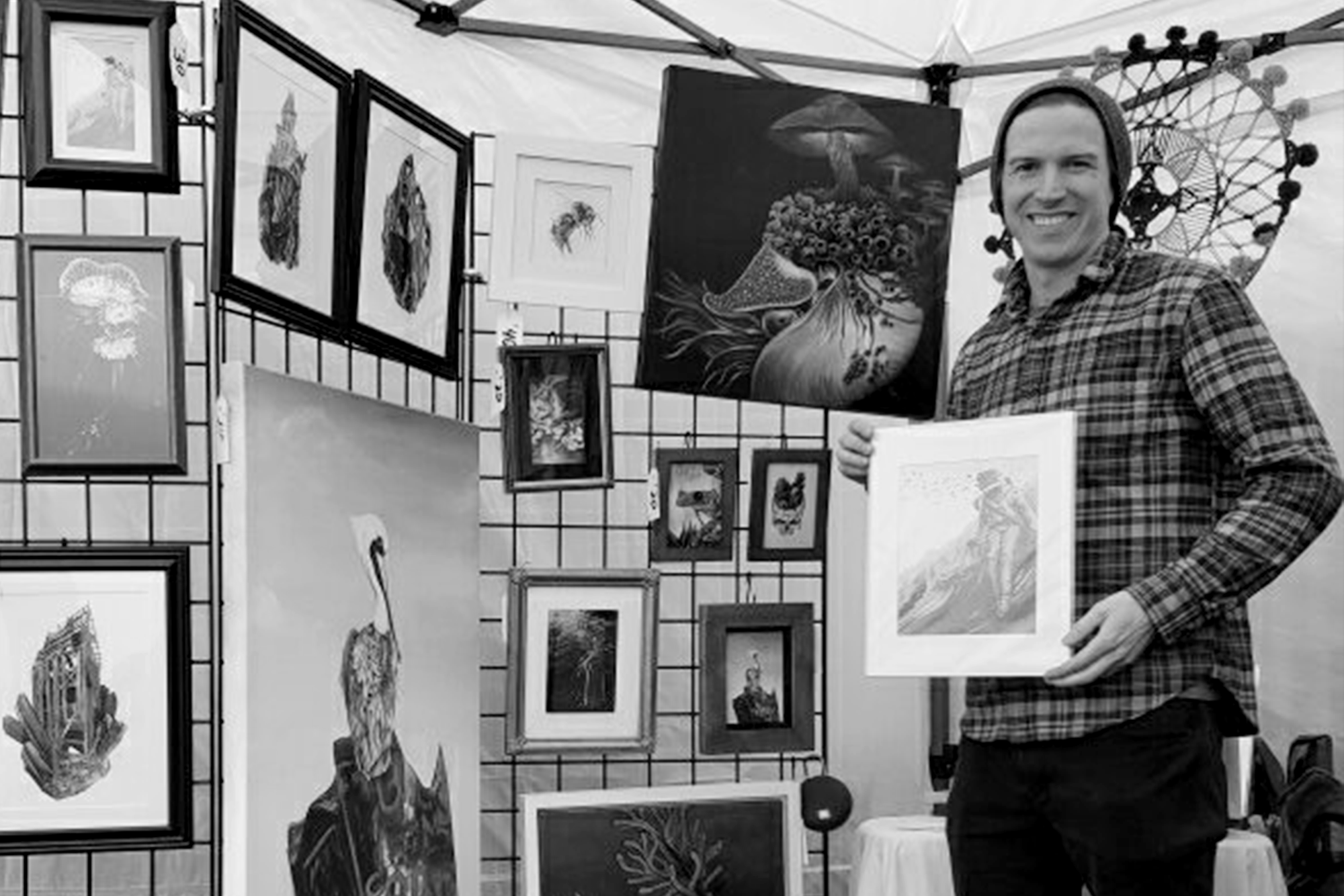 Ryan Breault standing next to artwork at a local market
